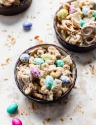 An Easter bunny trail mix in two small black bowls against a white background with toasted coconut around each bowl.