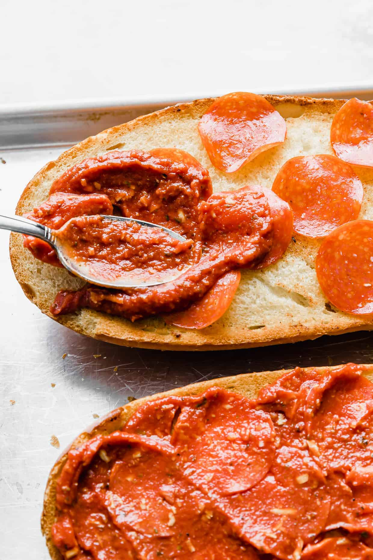 A spoon spreading pizza sauce overtop of pepperonis on a French bread loaf.