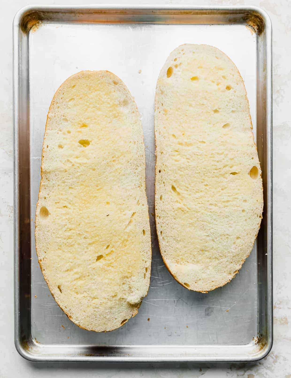Two open faced slices of French bread on a baking sheet.