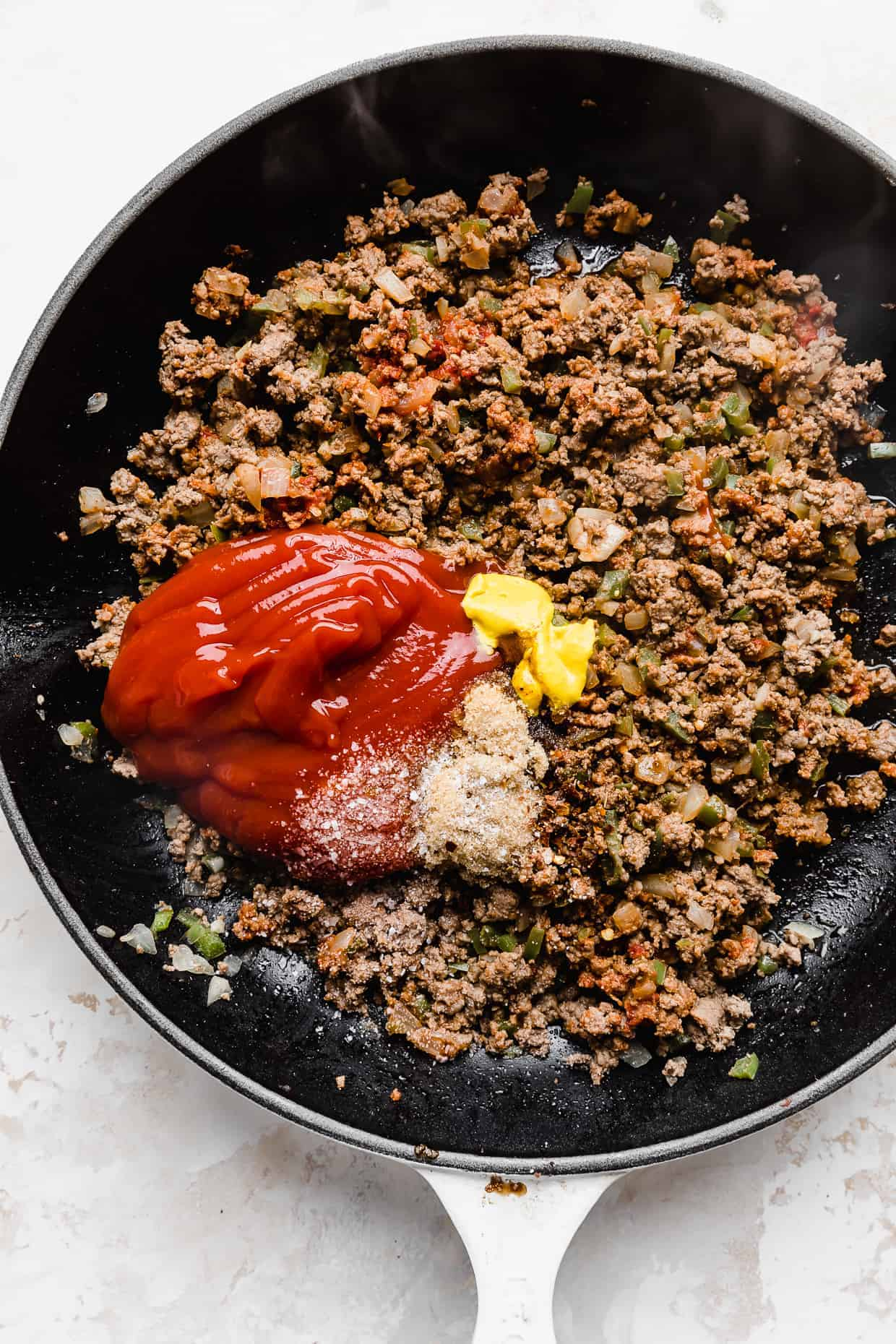 A skillet full of ground beef with ketchup, mayo, salt, and garlic to make sloppy joes.