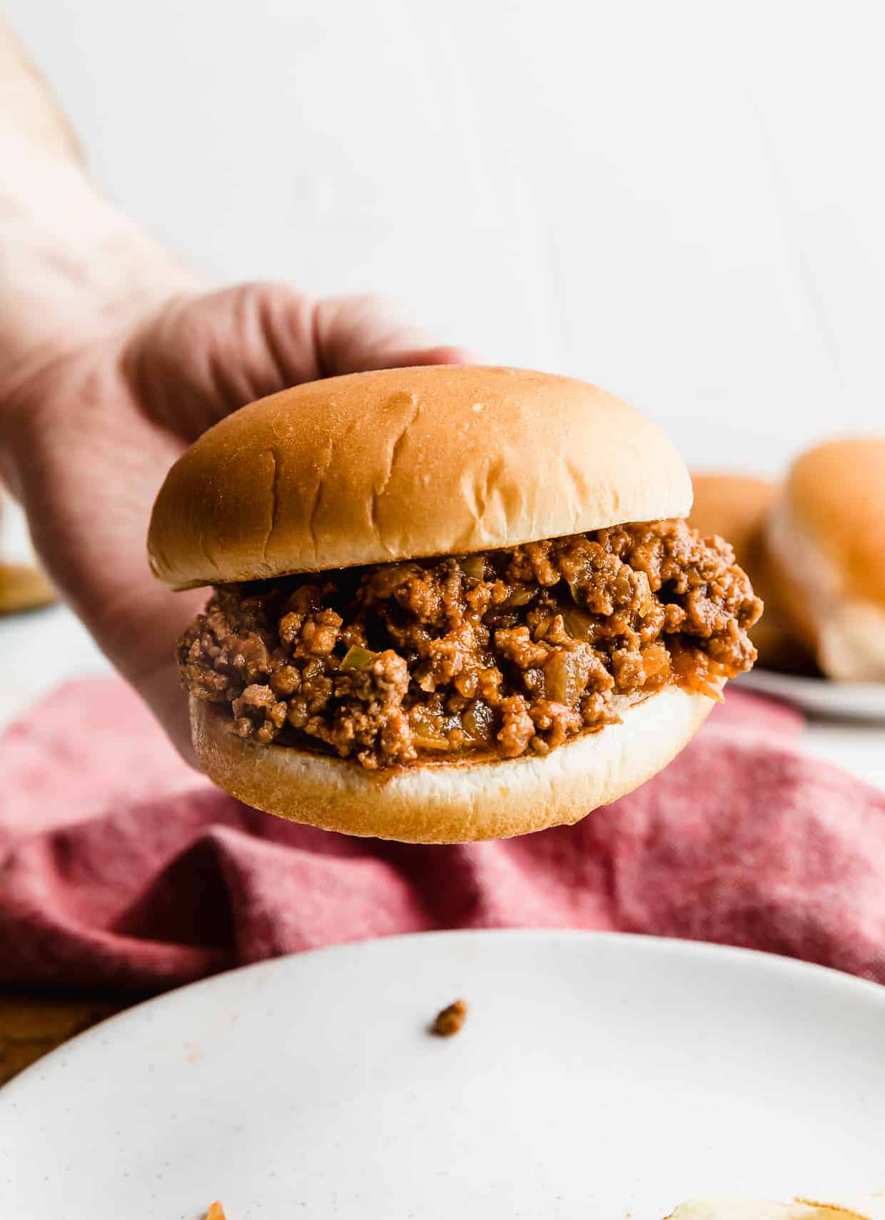 A hand holding up a hamburger bun that is very full of the best homemade sloppy Joe mix.