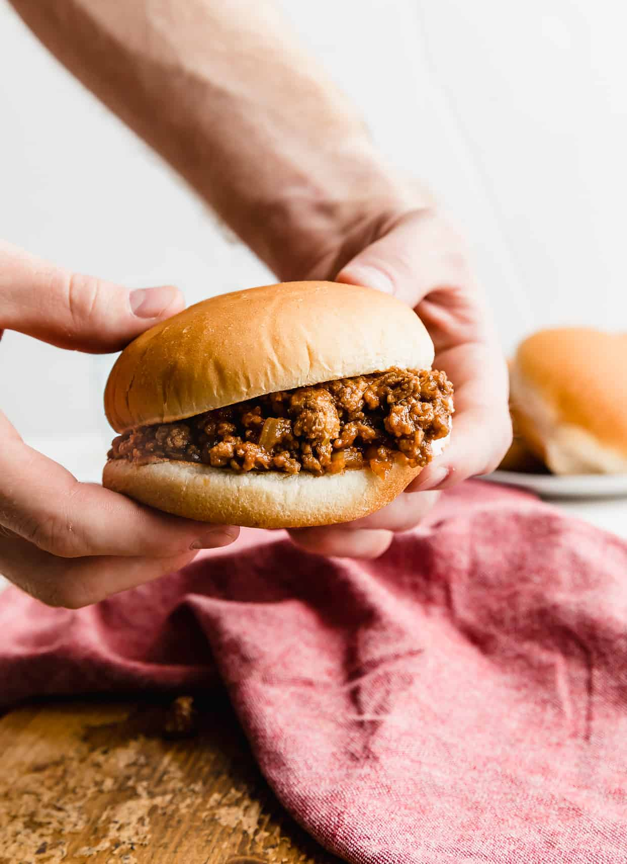 Two hands holding up a homemade sloppy Joe with a red napkin in the background.