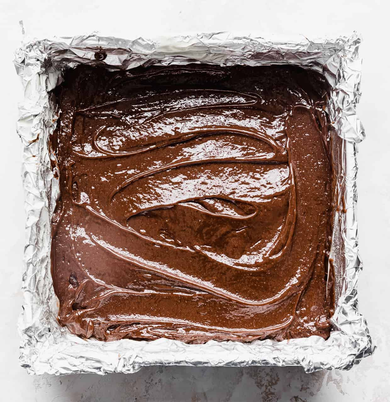 A foil lined square brownie pan with raw brownie batter inside.