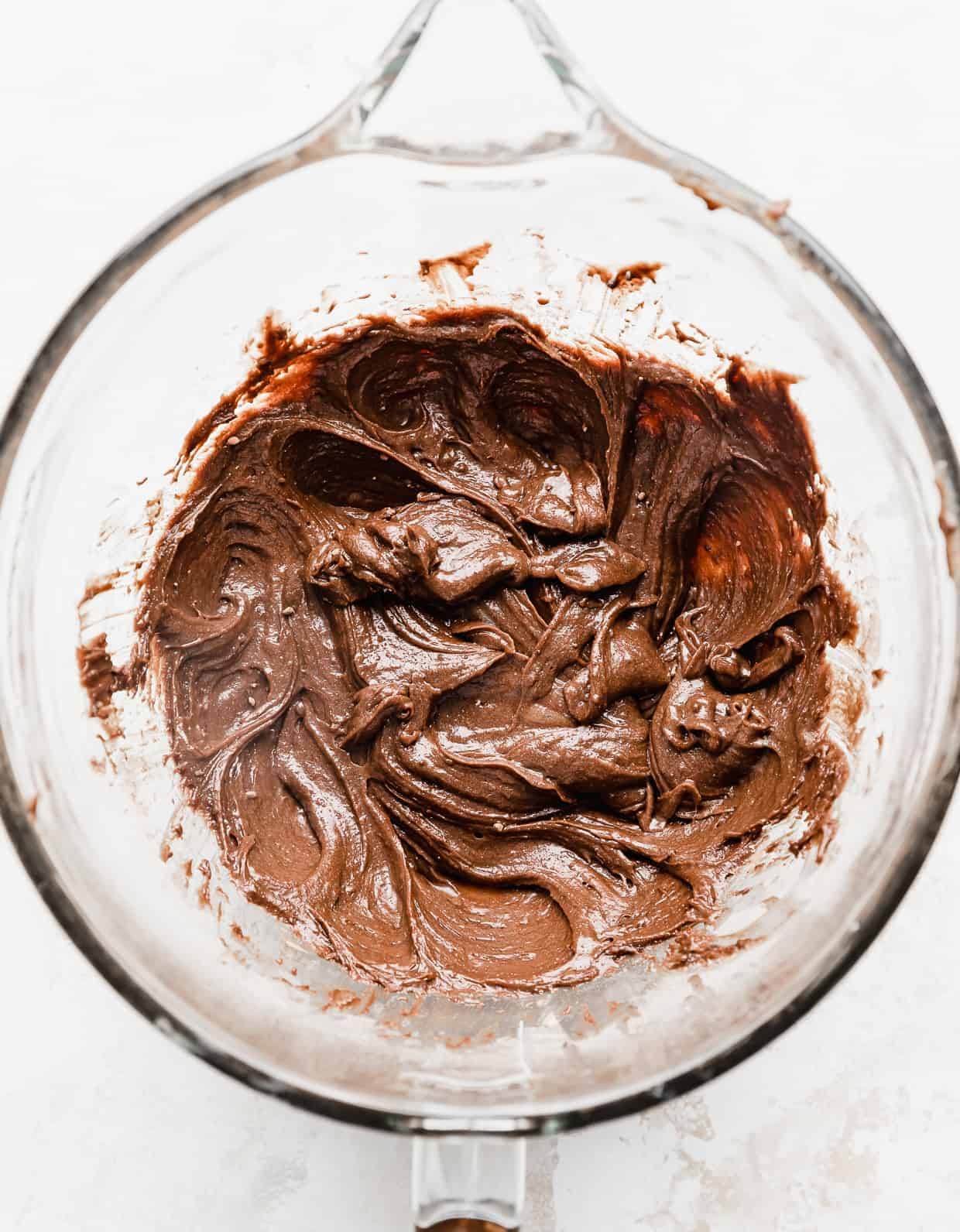 A glass mixing bowl full of lunch lady brownie batter, against a white background.
