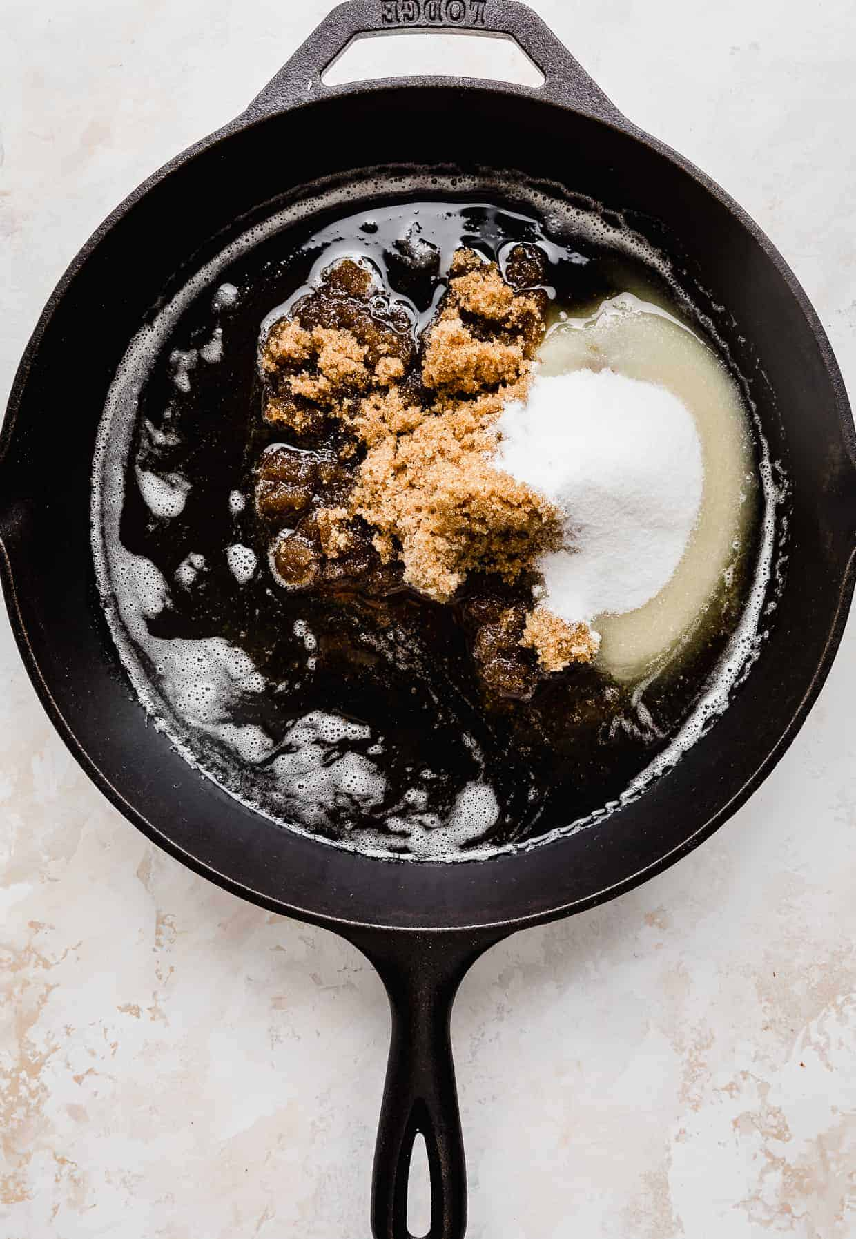 A black skillet with melted butter, sugar, and brown sugar in it.