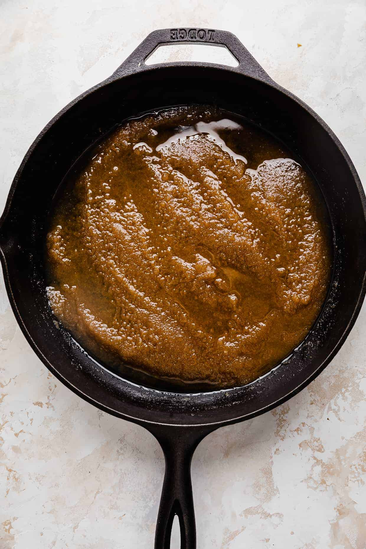 A cast iron skillet with a dark brown sugar and butter mixture spread along the bottom of the skillet.