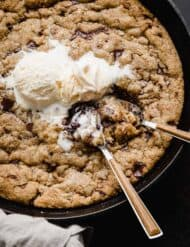 Two spoons scooping up skillet chocolate chip cookie that has been topped with vanilla ice cream.