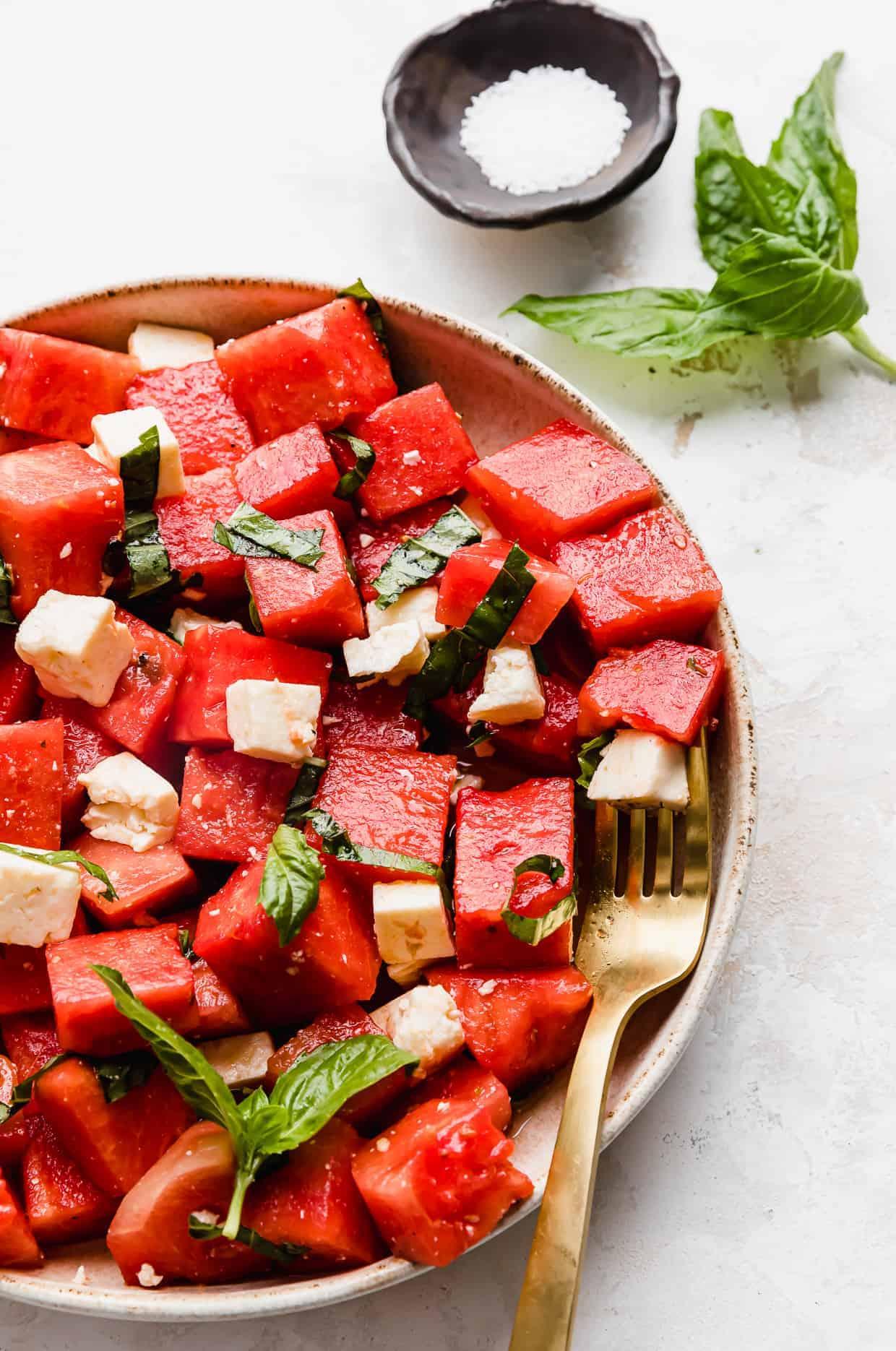 A close up photo of a cubed Watermelon Feta Basil Salad.