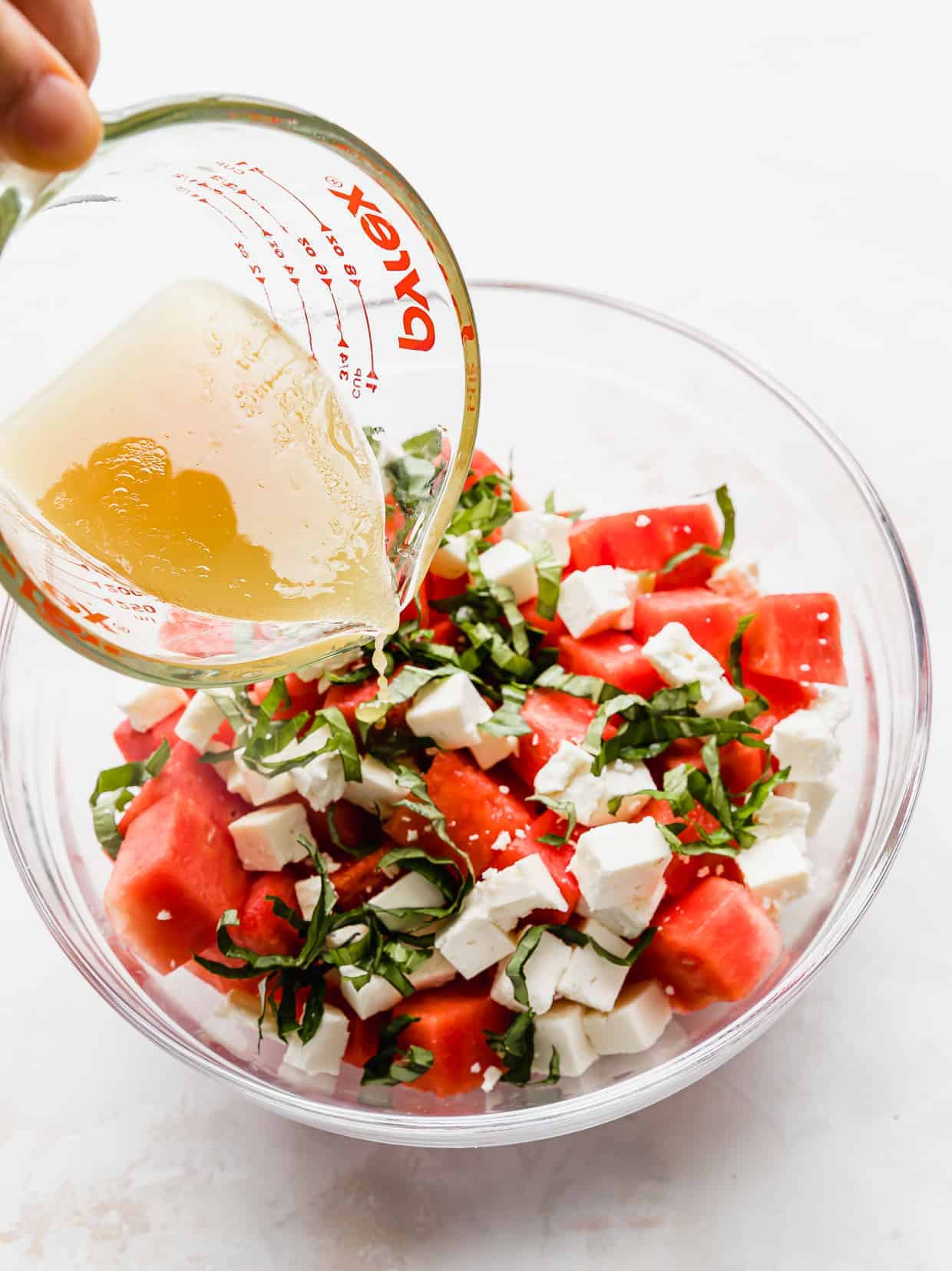 A dressing being poured over a Watermelon Feta Basil Salad in a glass bowl.