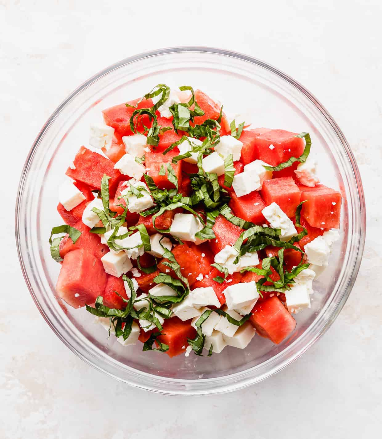 A glass bowl with chopped watermelon, basil, and feta in it.