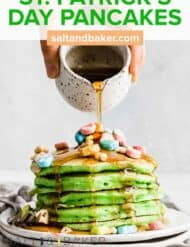A stack of green pancakes on a white plate, with lucky charms marshmallows overtop.