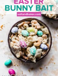 A black bowl full of a sweet and salty bunny bait easter snack mix against a textured white and cream background.