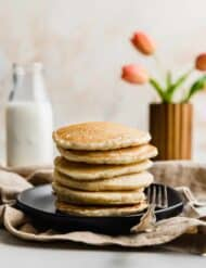 A stack of Almond Milk Pancakes on a black plate with pink tulips in the background.