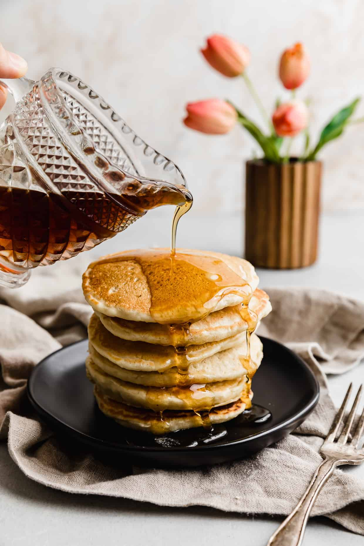 Maple syrup being poured overtop of Almond Milk Pancakes on a black plate.