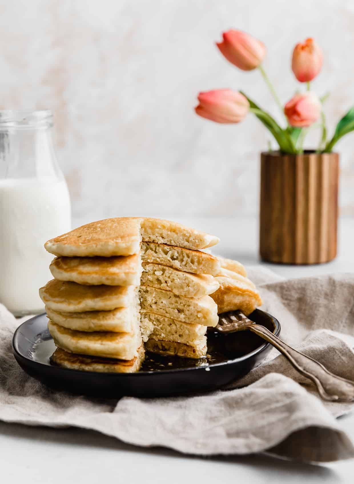 Fluffy Almond Milk Pancakes on a black plate with a wedge of pancake cut out of the stack.
