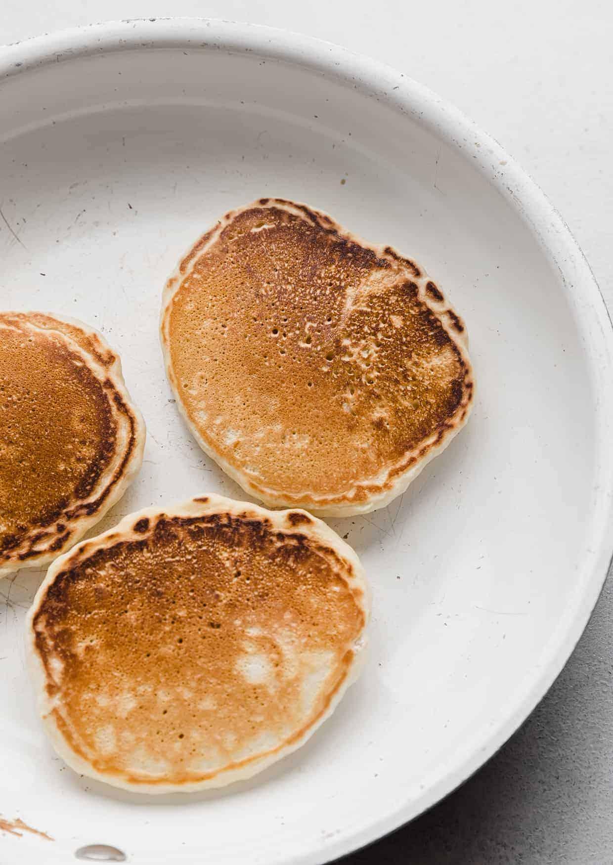Three golden brown Almond Milk Pancakes in a white skillet.