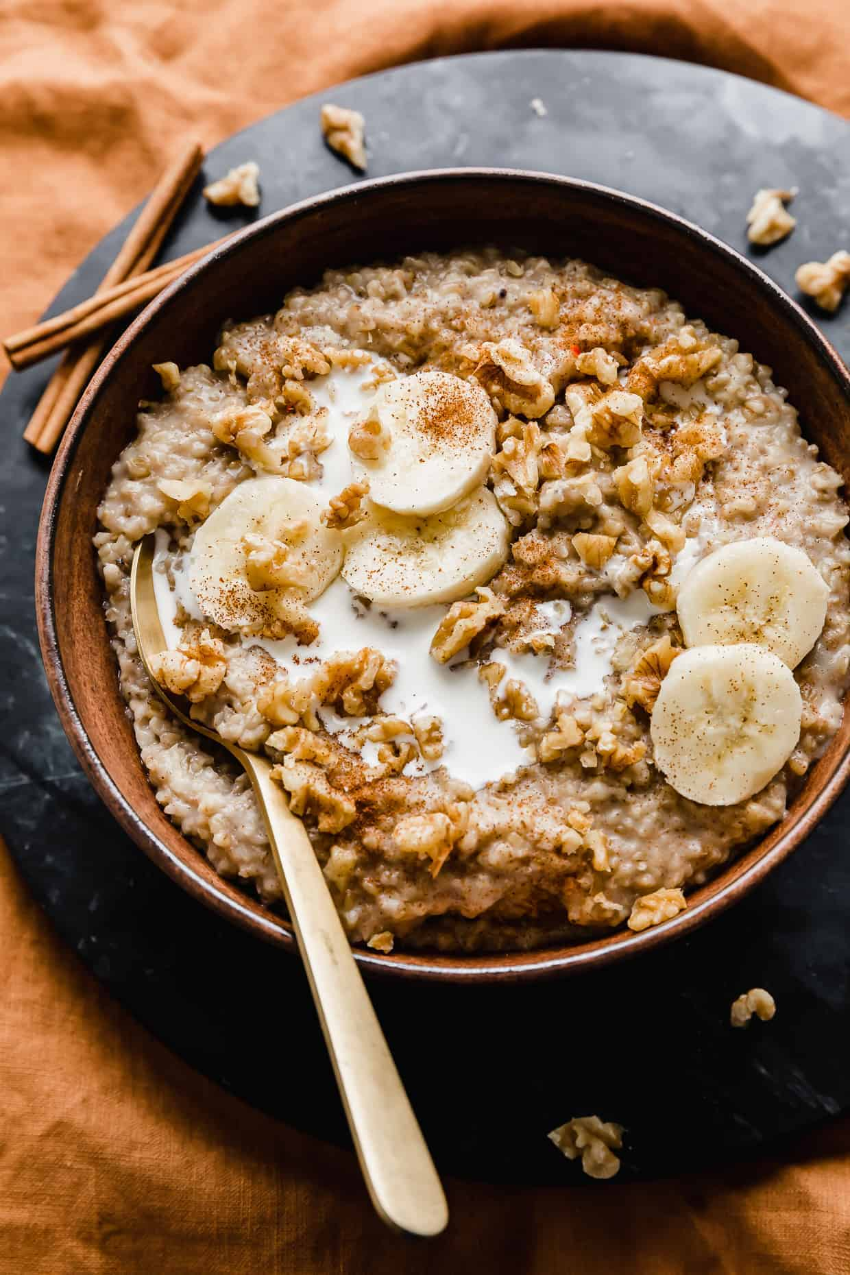 A wooden bowl full of Banana Steel Cut Oats topped with sliced bananas and walnuts against a black background.
