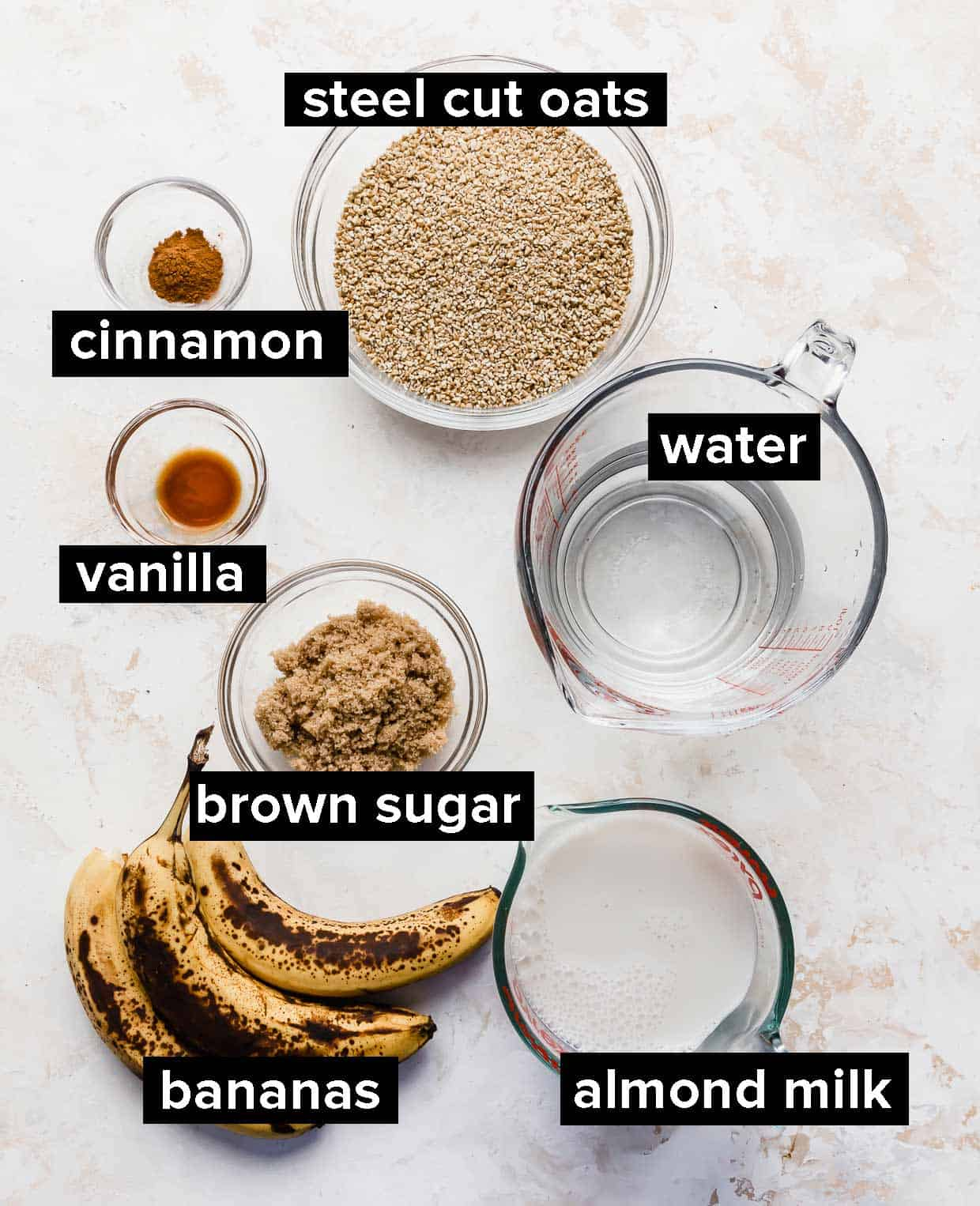 Ingredients used to make banana steel cut oats on a white background.