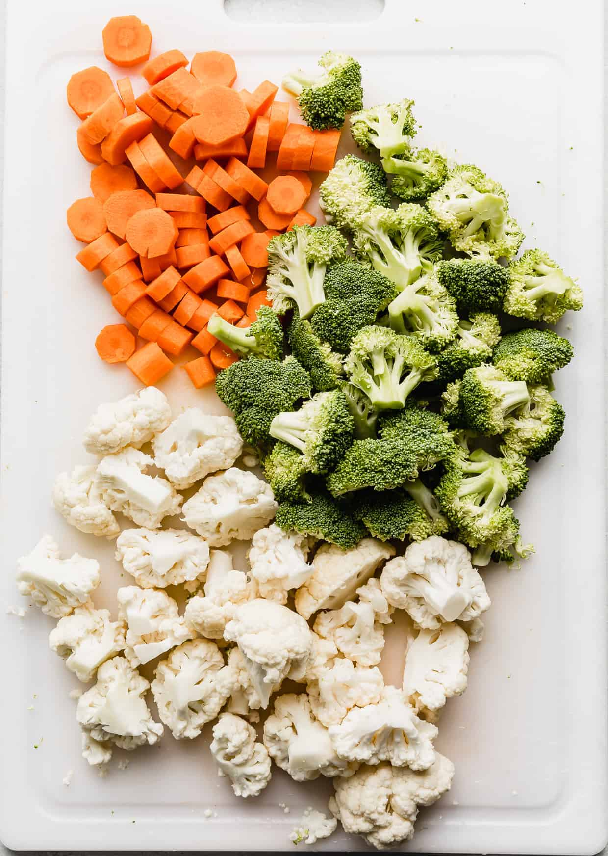 Chopped cauliflower, broccoli, and carrots on a white cutting board.
