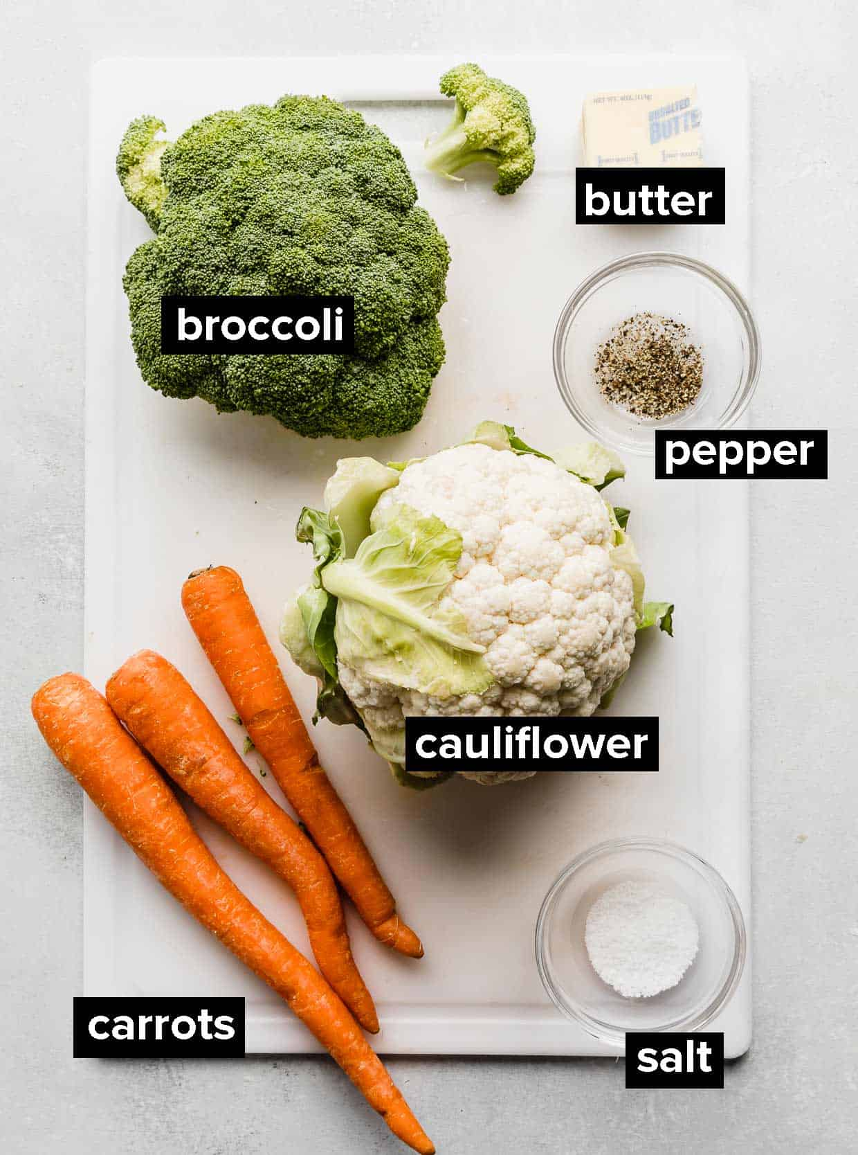 Ingredients used to make buttered vegetables on a white cutting board.