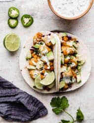 Two Roasted Cauliflower Tacos topped with a drizzle of lime crema against a white background.