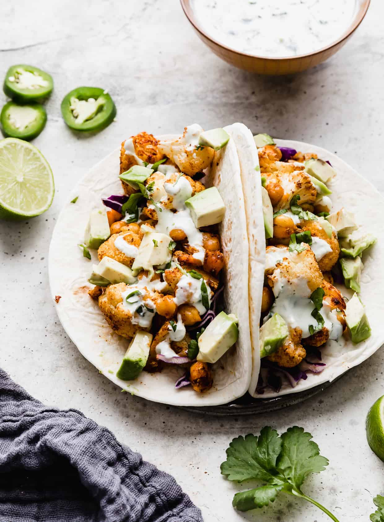 Two cauliflower tacos on a plate. A bowl of white sauce is in the background as well as sliced jalapeños.