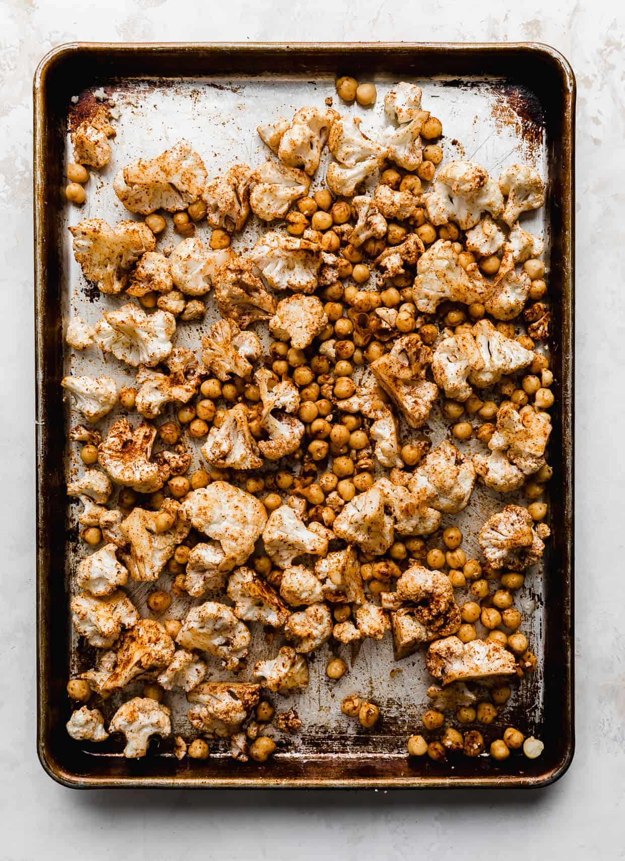 A baking sheet full of roasted cauliflower florets and chickpeas.