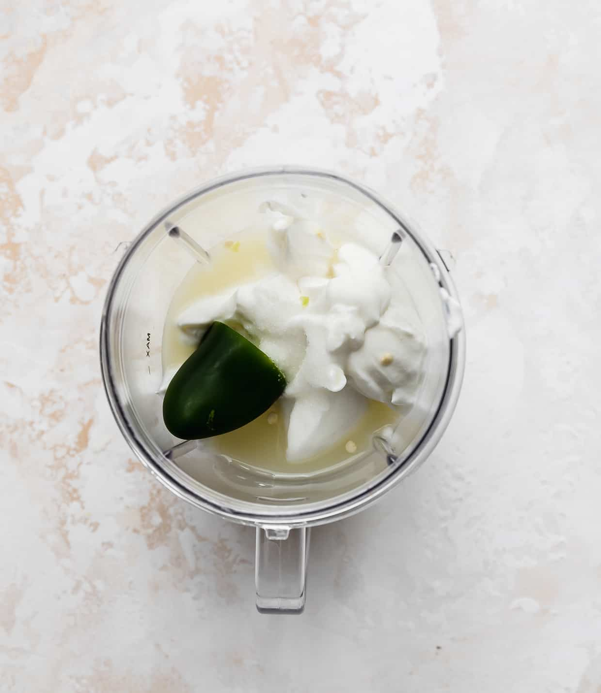 A small blender with white yogurt, half of a jalapeño, and lime juice in it.
