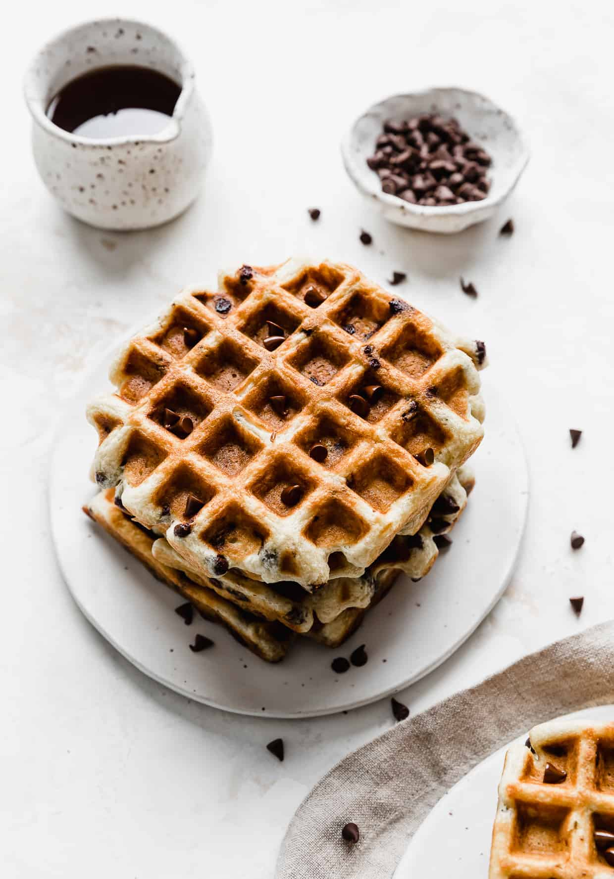 A stack of square Chocolate Chip Waffles on a white plate with syrup in the background.