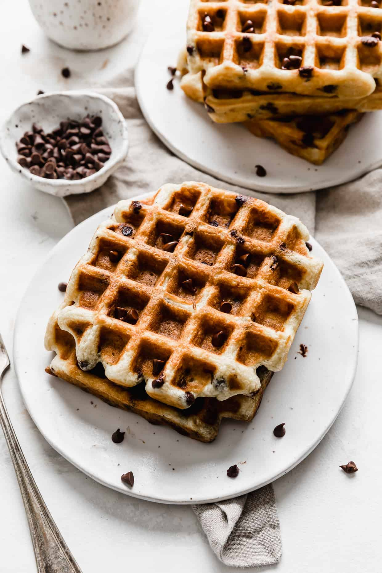 A stack of Chocolate Chip Waffles on a white plate.