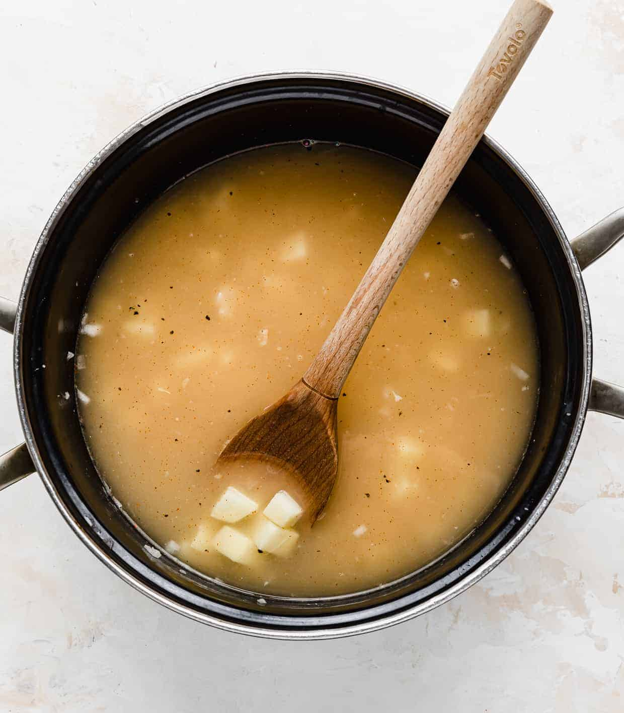 A pot with chicken broth and diced potatoes in it.