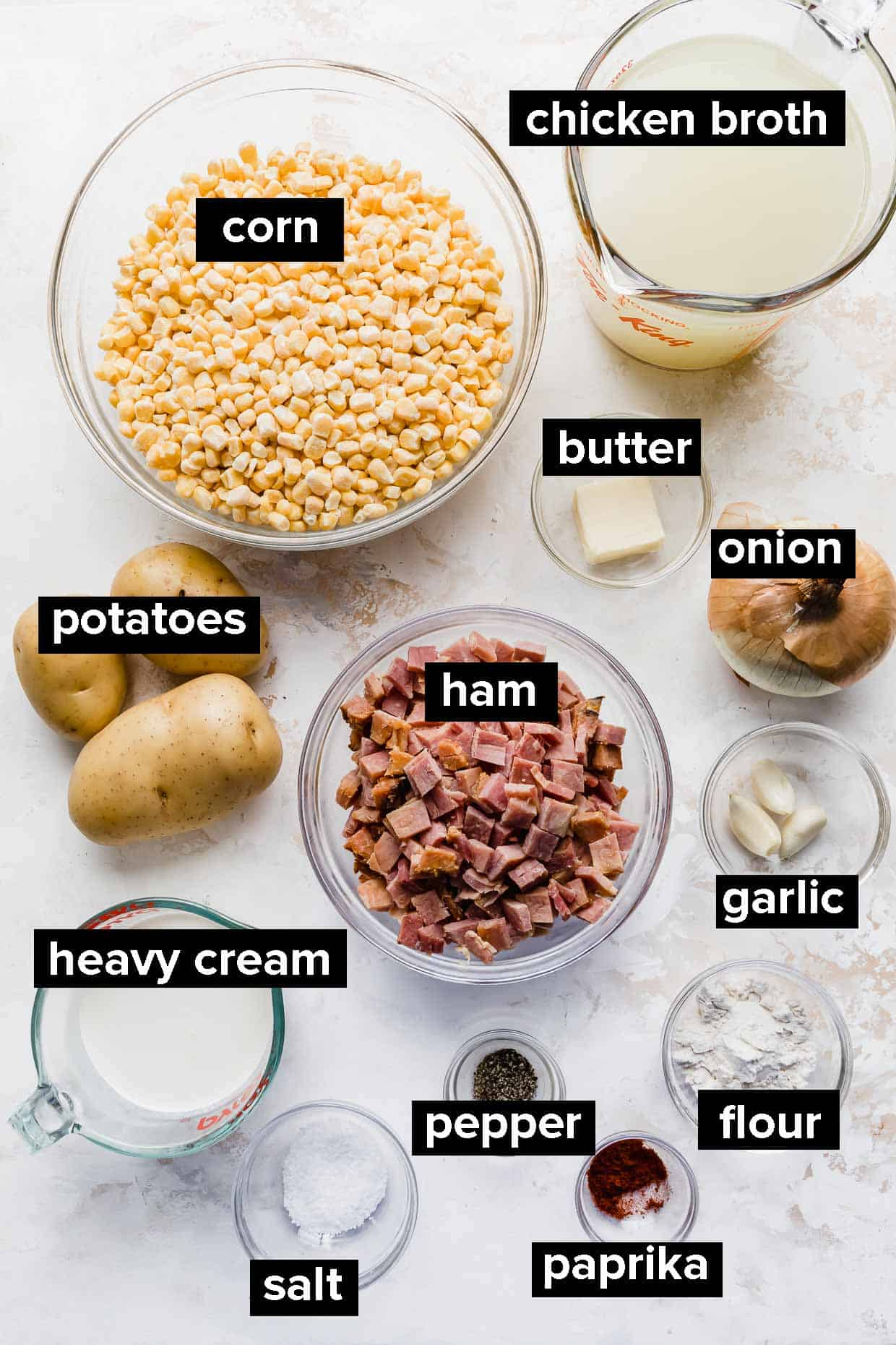 Ingredients used to make ham and corn chowder on a white background.