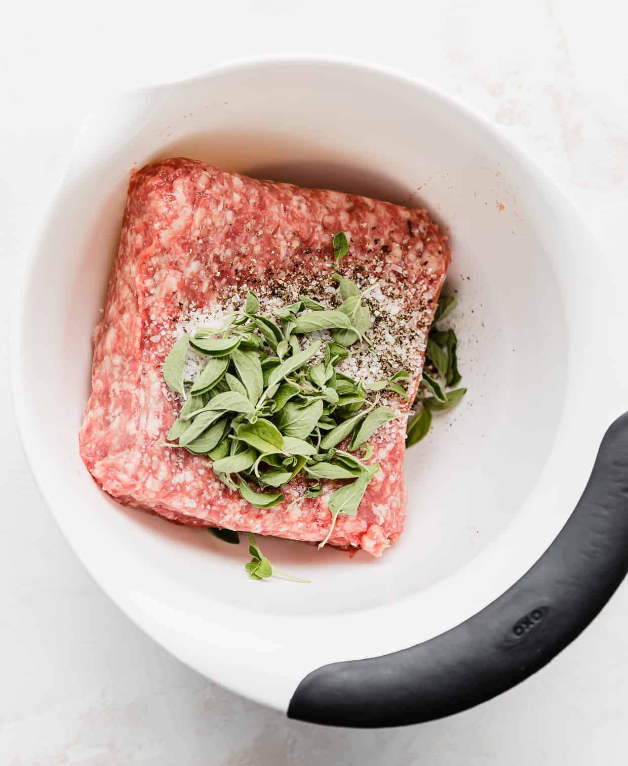 A white bowl with ground lamb, fresh herbs and seasonings in it.