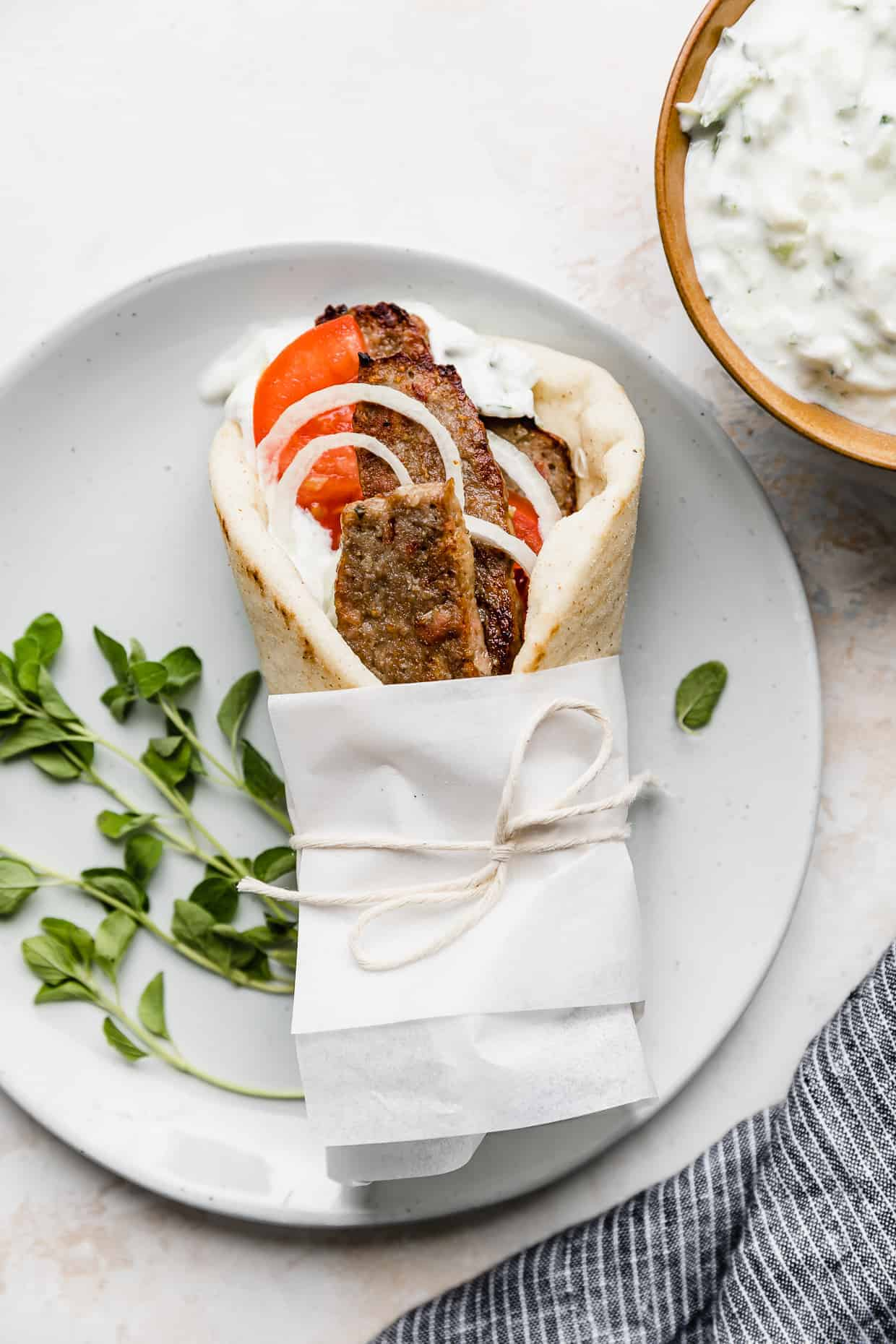 A lamb gyro wrapped in white parchment paper on a white plate.