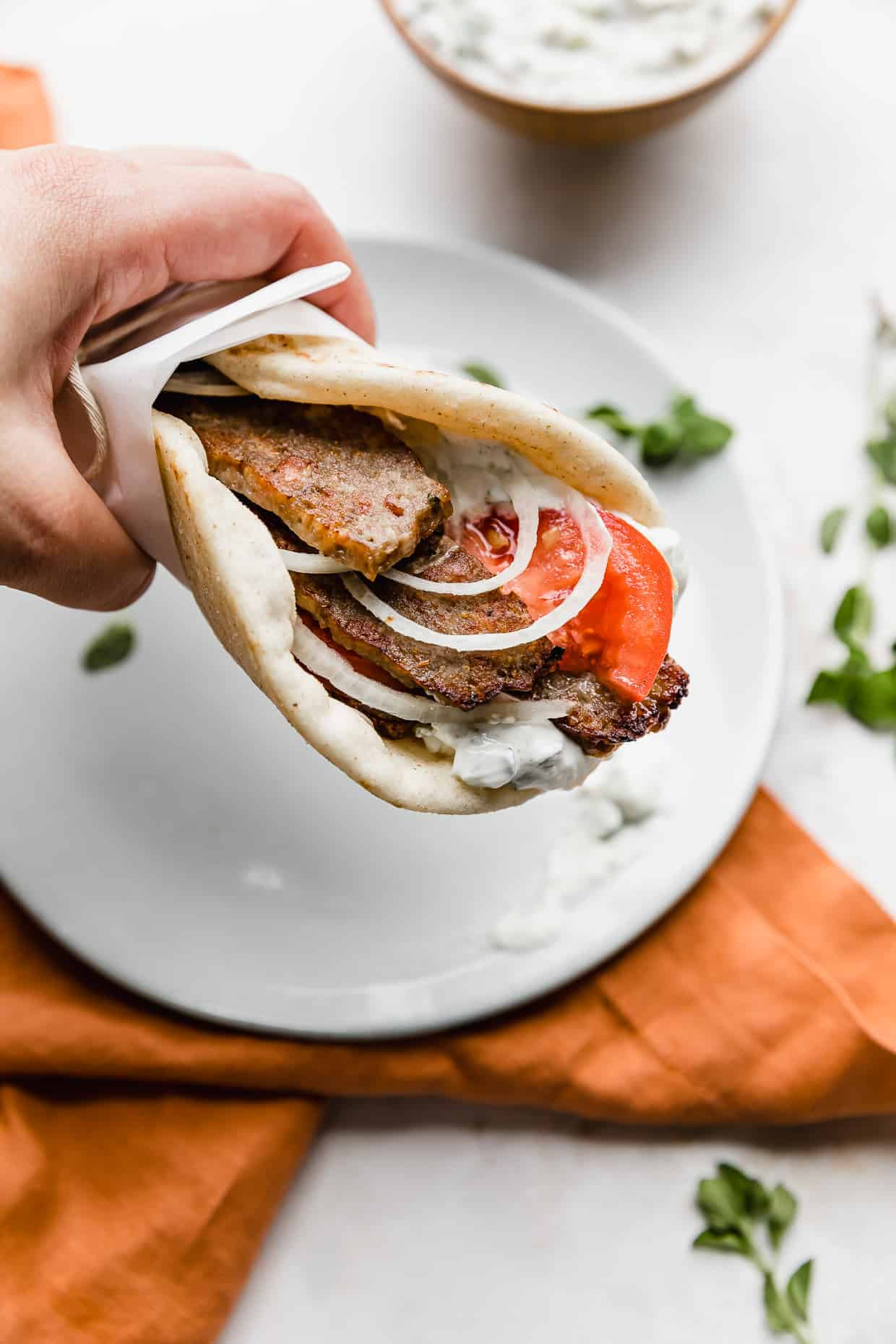 A hand holding up a greek lamb gyro in a flat bread.