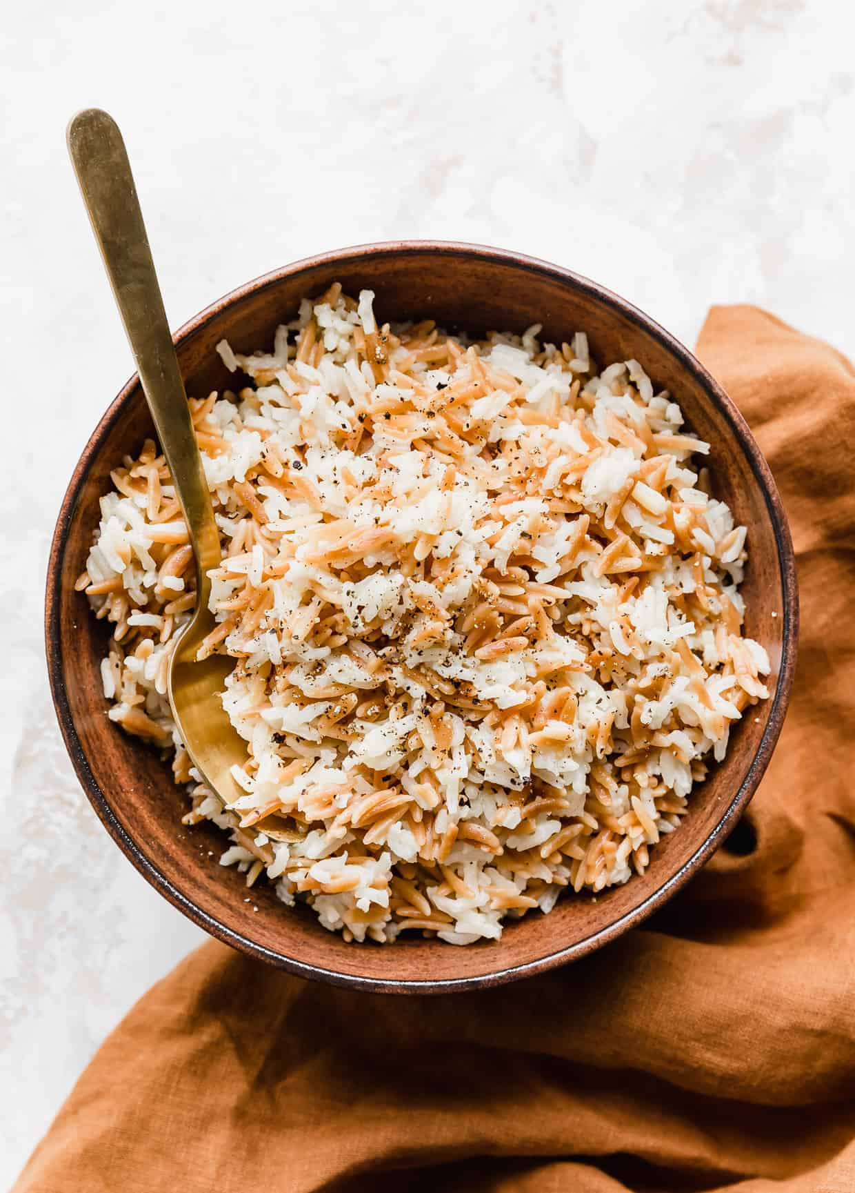 Orzo rice in a brown bowl with a golden spoon inside the bowl.