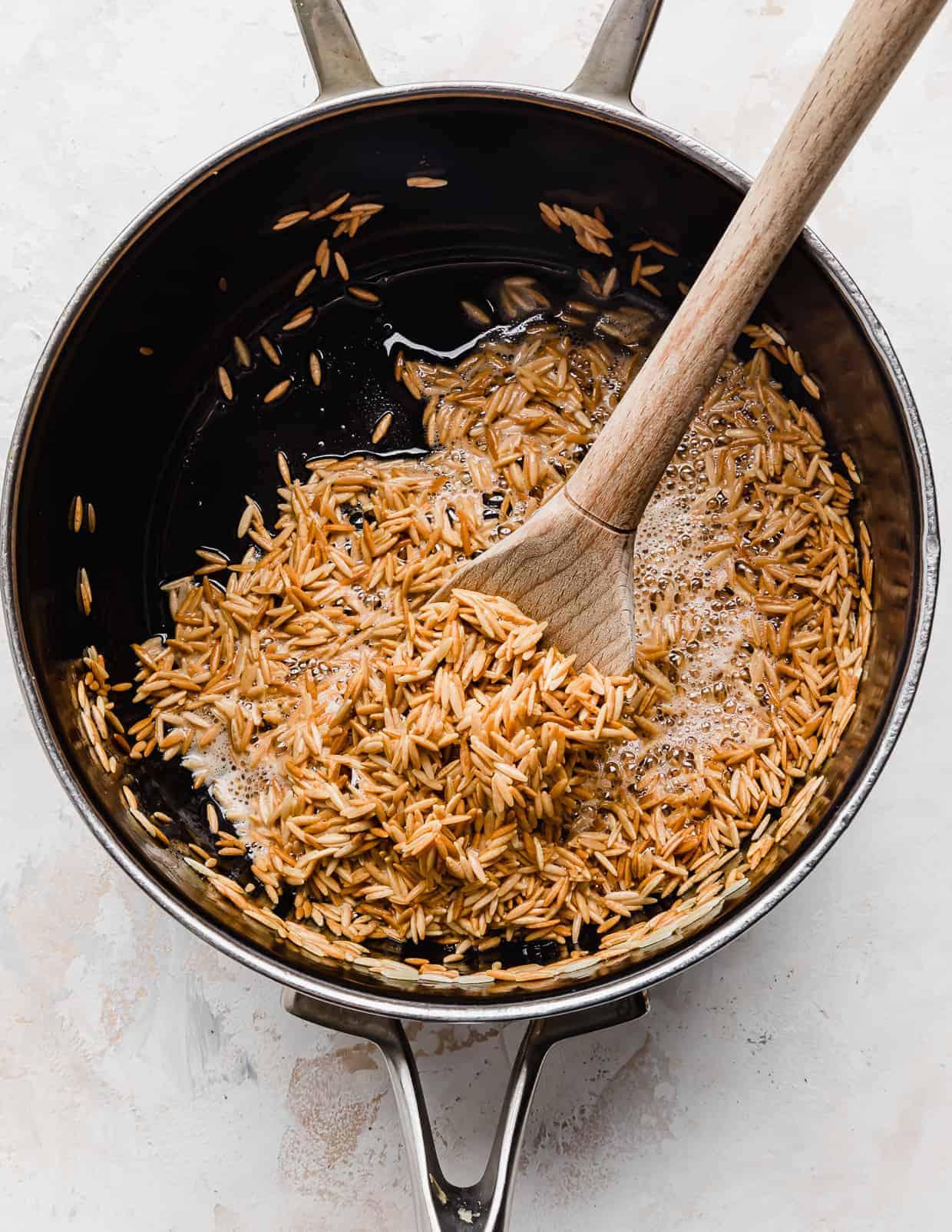 Golden brown orzo rice in a saucepan.