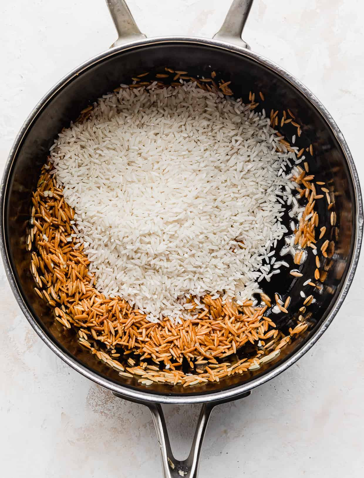 White rice in a saucepan, overtop of golden brown orzo pasta.