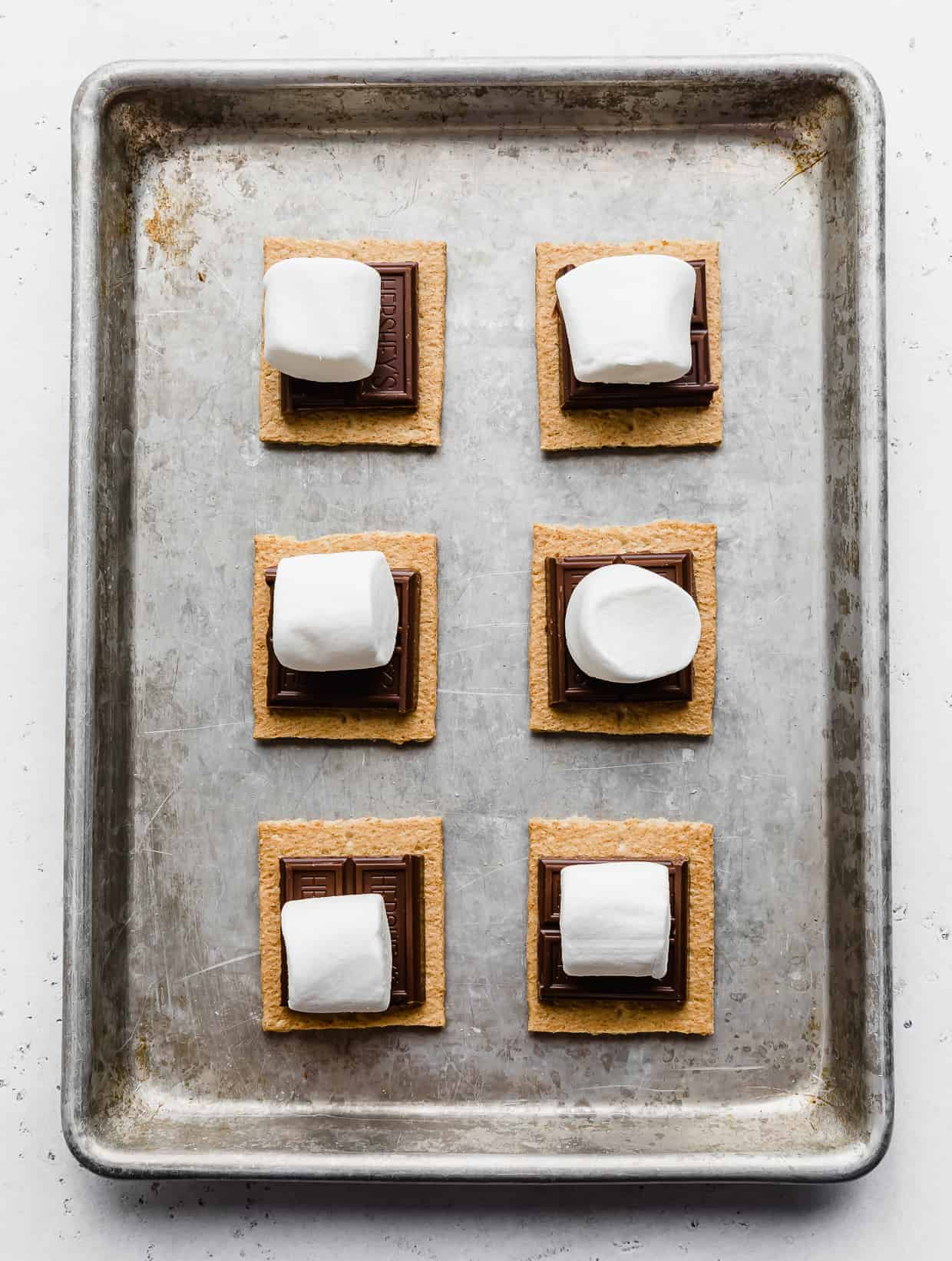 Large marshmallows on top of chocolate and graham cracker squares.
