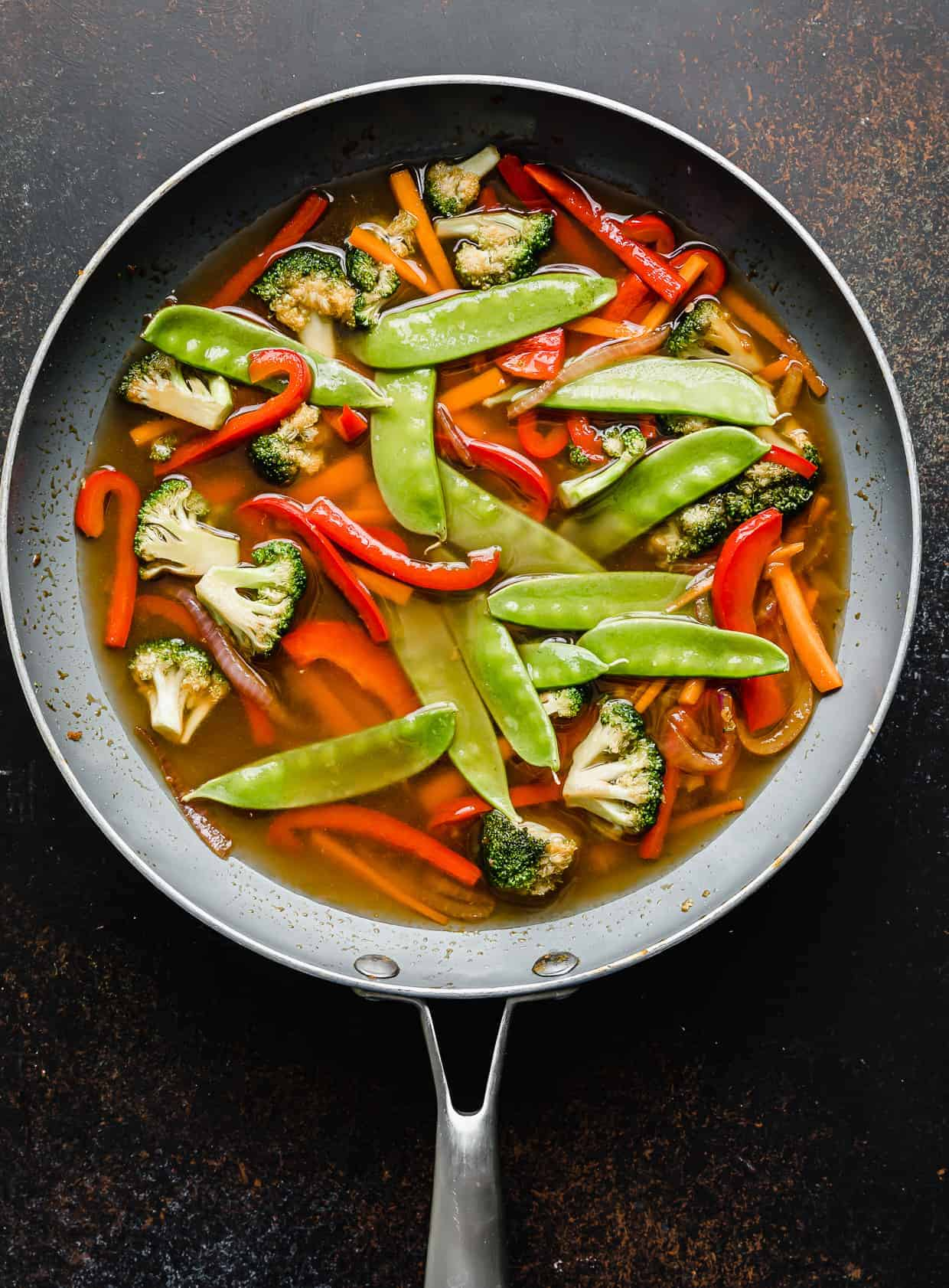 Snow peas and water added to a skillet with vegetables.