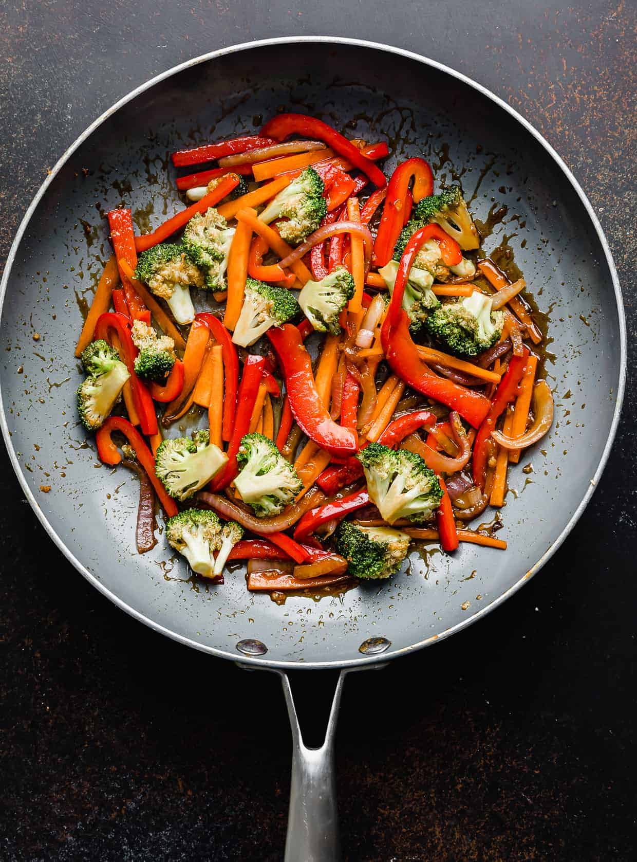 Cooked red peppers, broccoli, and carrots in a skillet.