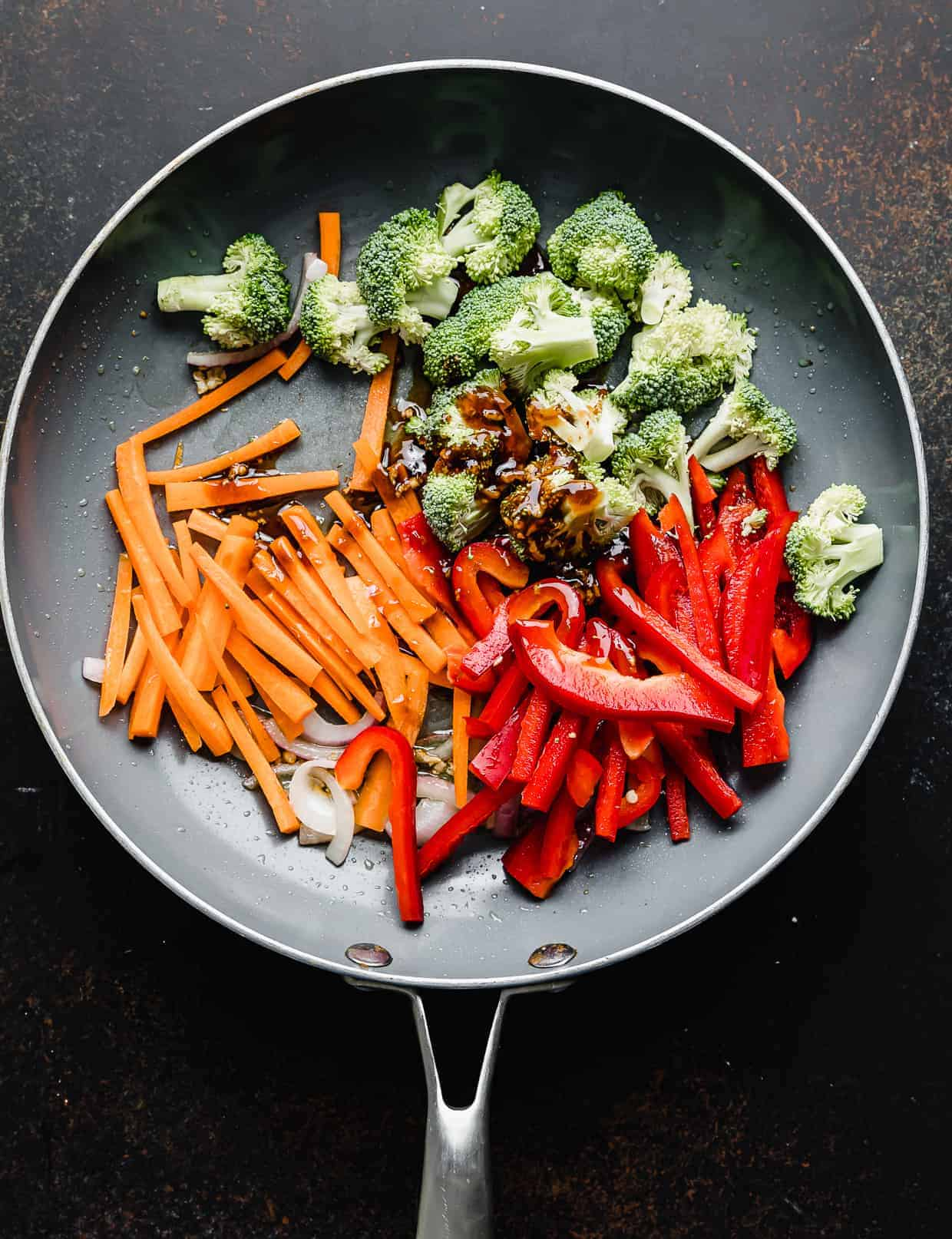 A skillet with red peppers, broccoli, carrots, and a brown sauce in it.