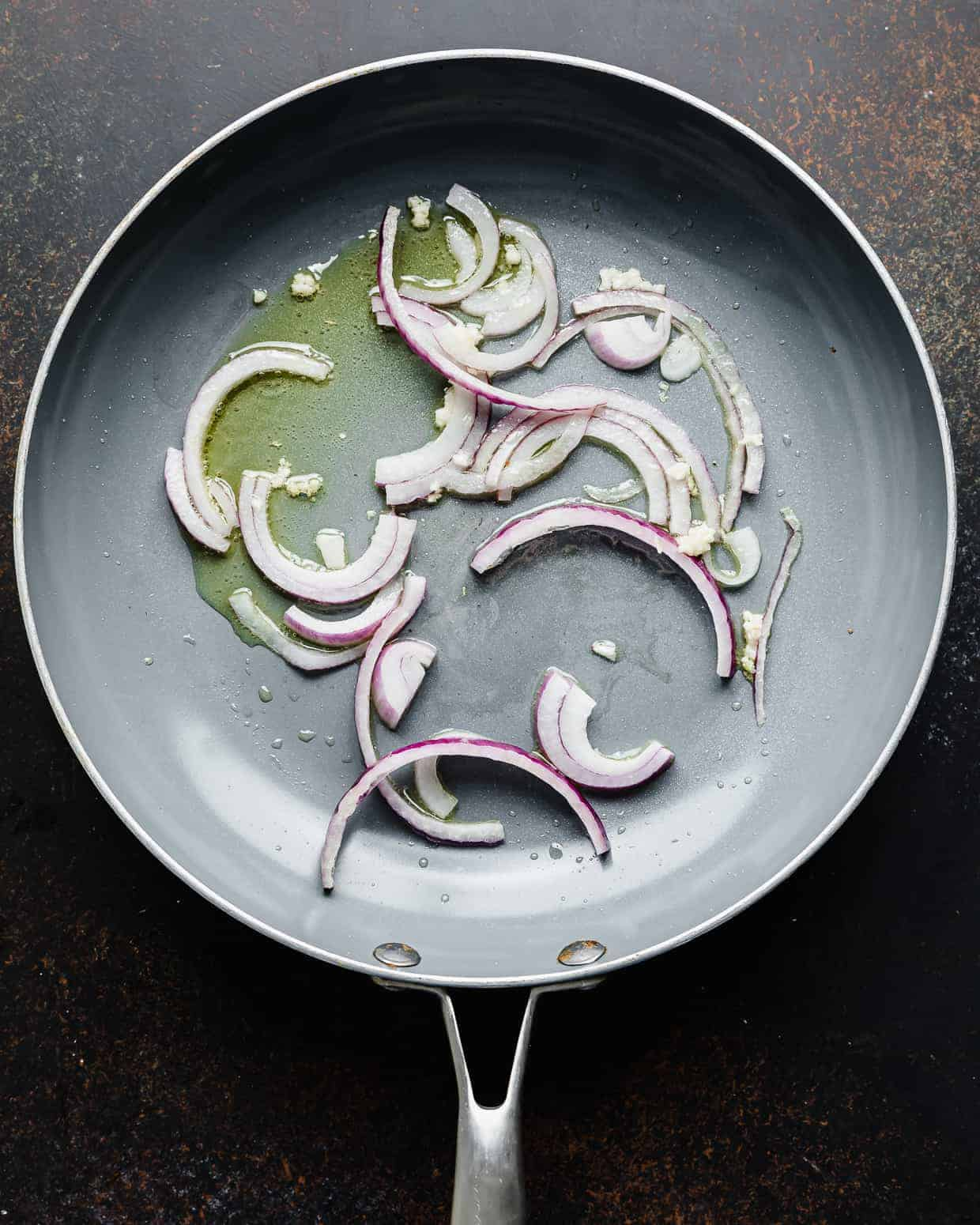 A gray skillet with sliced red onions and minced garlic in it.