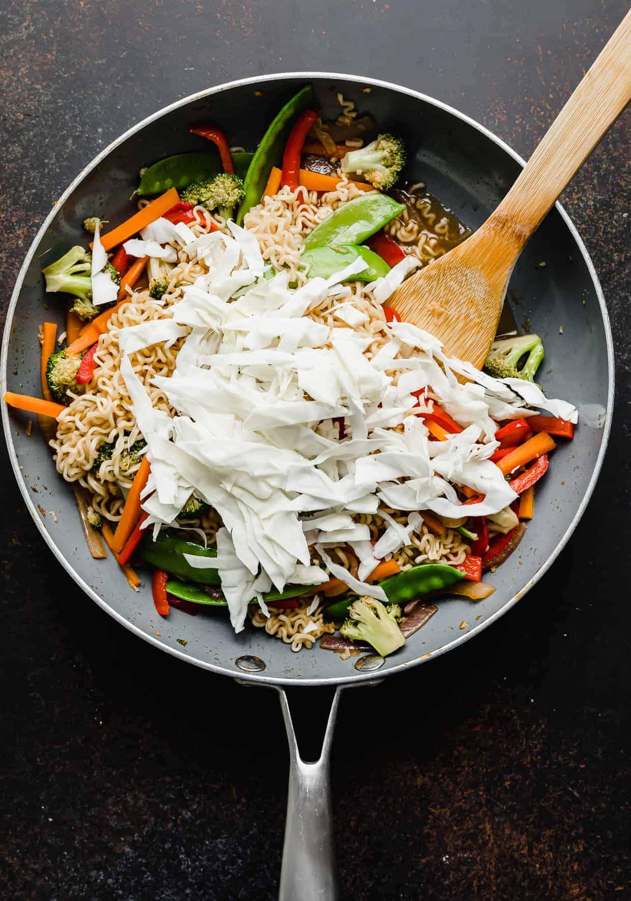 Sliced cabbage overtop Ramen with Vegetables.