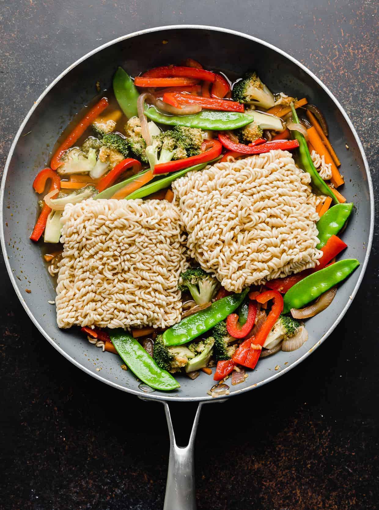 Two ramen noodles bundles in a skillet overtop sliced vegetables.