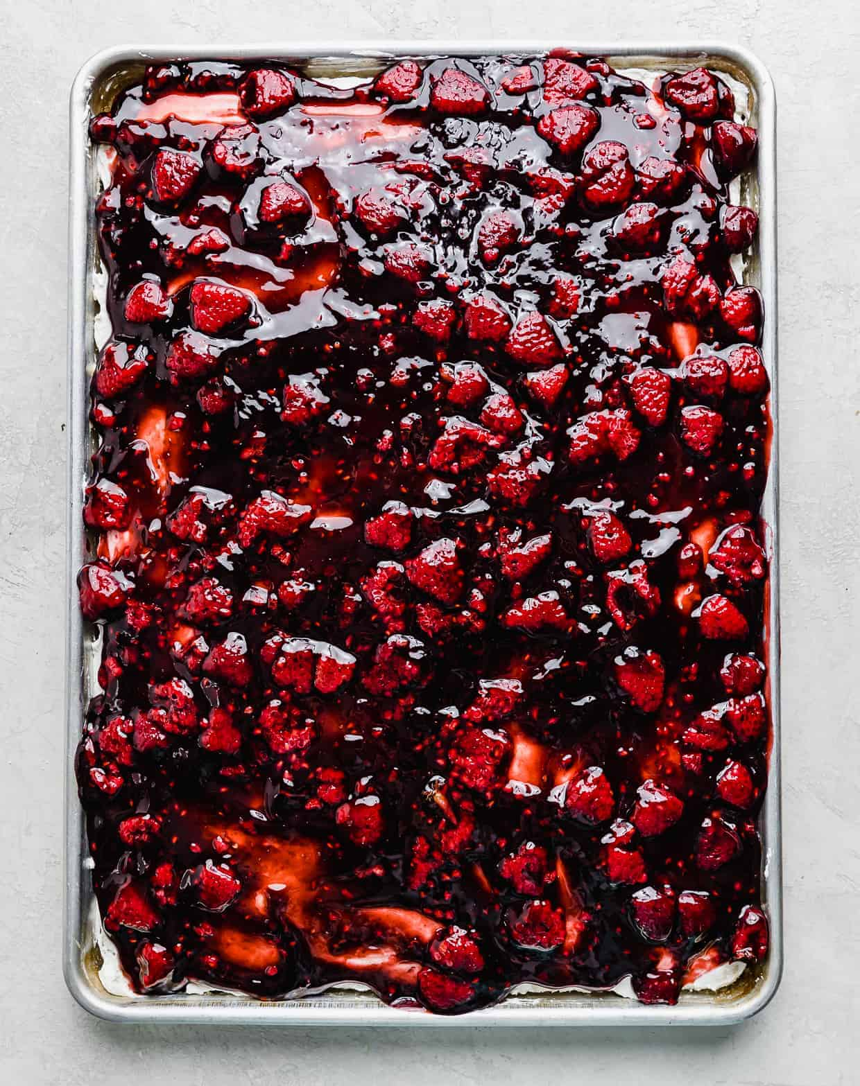 A deep red colored gelatin raspberry sauce spread overtop a baking sheet.