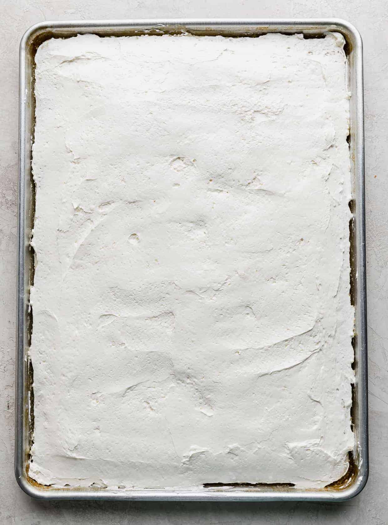 A white sheet cake topped with a white cream cheese layer.