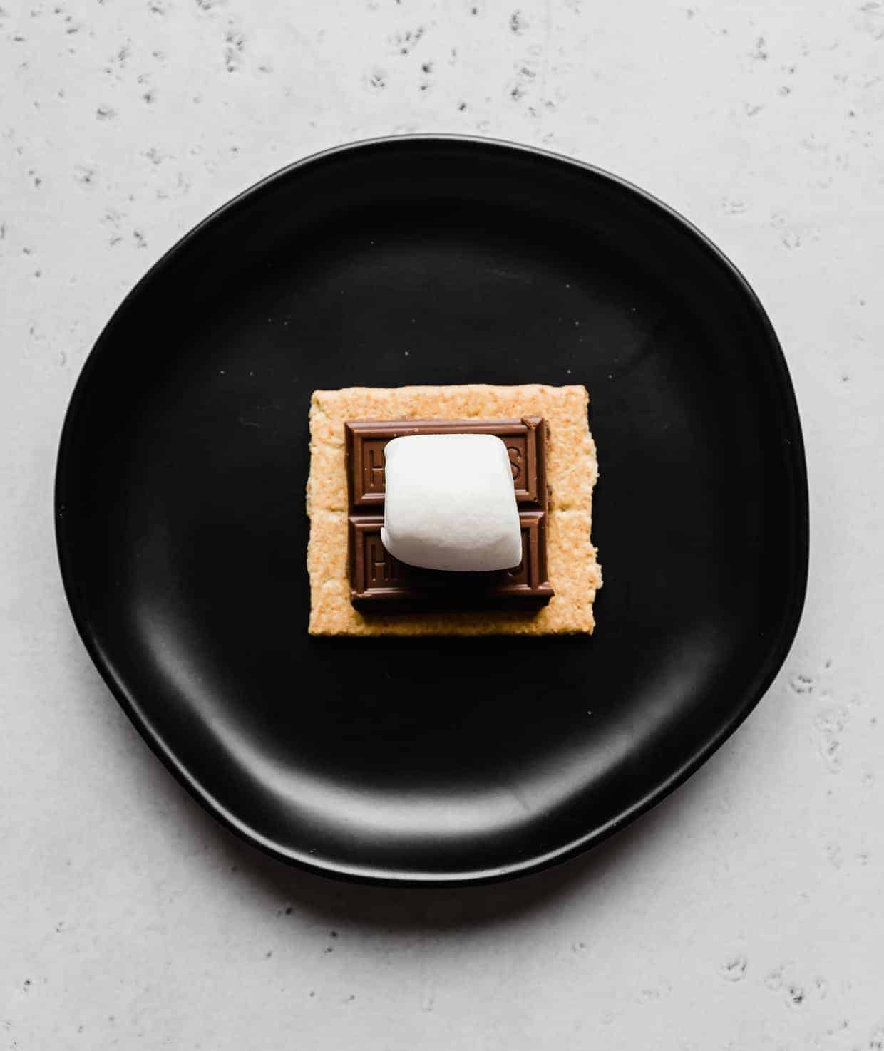 A black plate with a graham cracker square, chocolate piece, and large mallow.