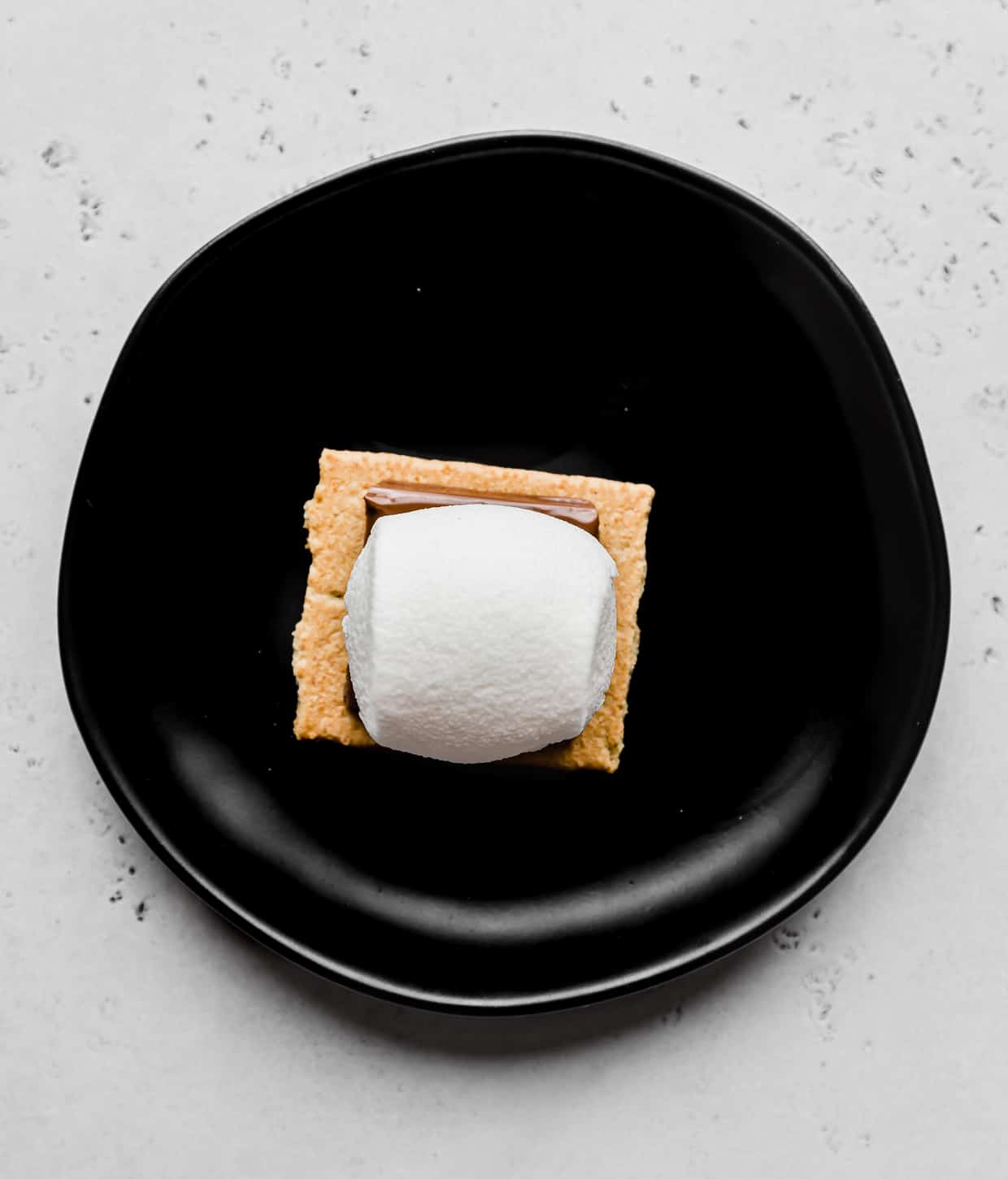 A marshmallow atop a chocolate square that's on top of a graham cracker.