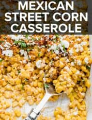 Mexican Street Corn casserole in a white dish topped with chili powder and cilantro.